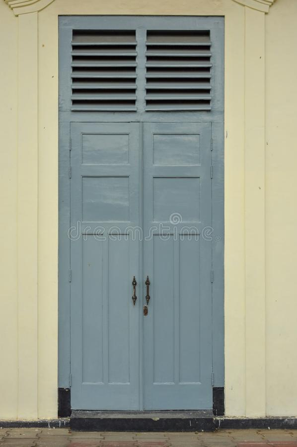 Ancient gray door with ventilation holes above it stock photo