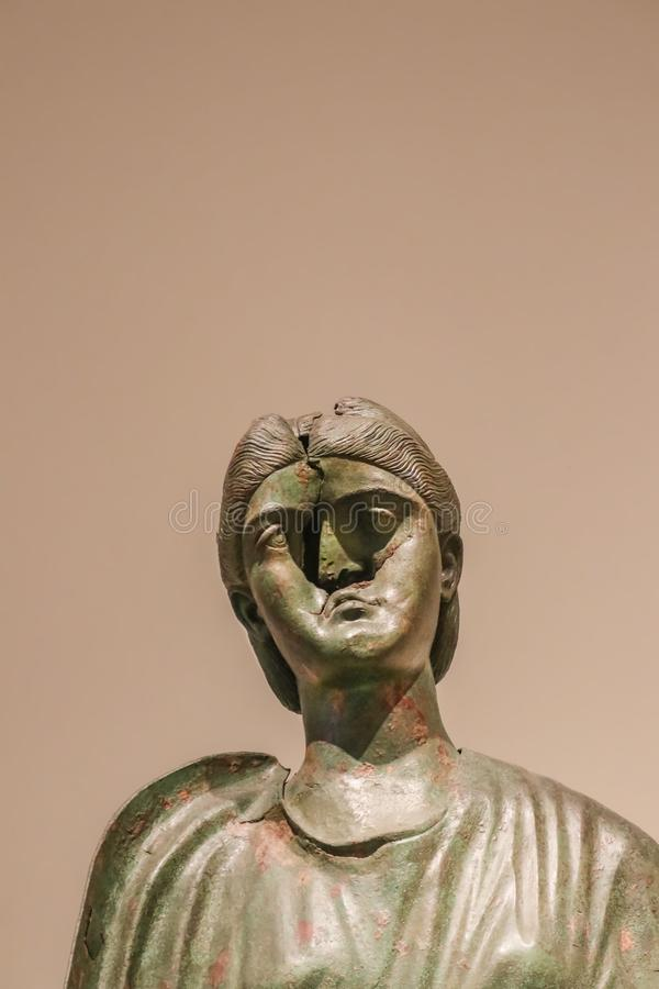 Ancient Greek brass sculpture of woman with a bashed in face against tan background - room for copy stock image