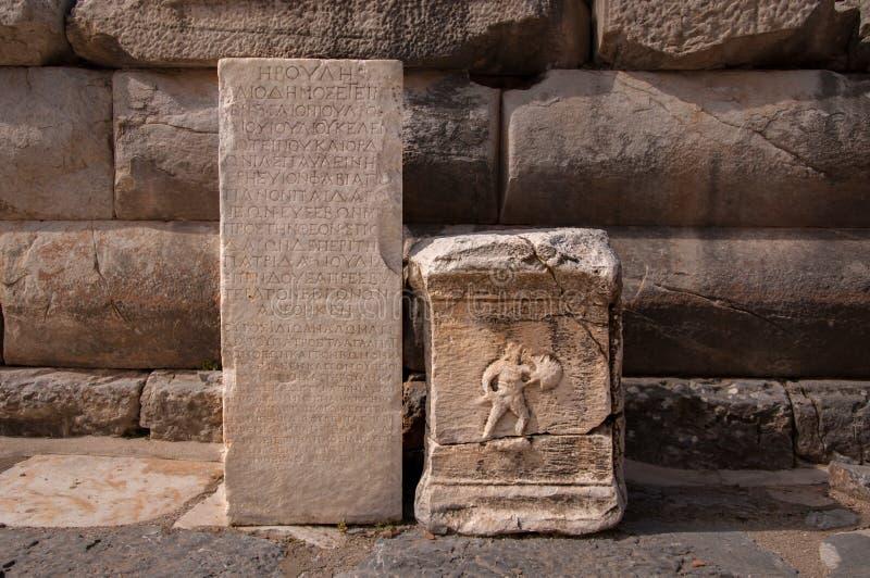 Ancient greek inscription and gladiator figure on block stones from Ephesus, Turkey royalty free stock photo