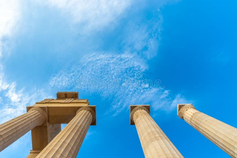 Ancient greek pillars of the acropolis of Lindos. View from below towards a blue sky of an ancient greek pillars of the acropolis of Lindos stock images