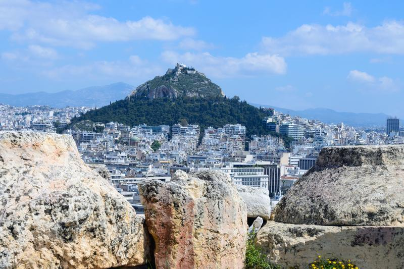 Ancient Greek ruins, ruins amidst lush green grass. Acropolis, Athens, Greece. Beautiful view of the capital of Greece - Athens from the slopes of the royalty free stock images