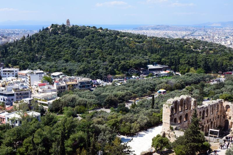 Ancient Greek ruins, ruins amidst lush green grass. Acropolis, Athens, Greece. Beautiful view of the capital of Greece - Athens. From the slopes of the royalty free stock image