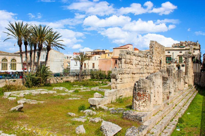 Ancient Greek ruins of the Temple of Apollo in Ortigia Island, Syracuse, Sicily, Italy photographed with adjacent palm trees. Colonnade ruins, significant royalty free stock photos