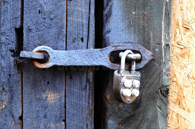 The ancient hinged iron castle on a door or gate. The closed wooden doors close up royalty free stock photos