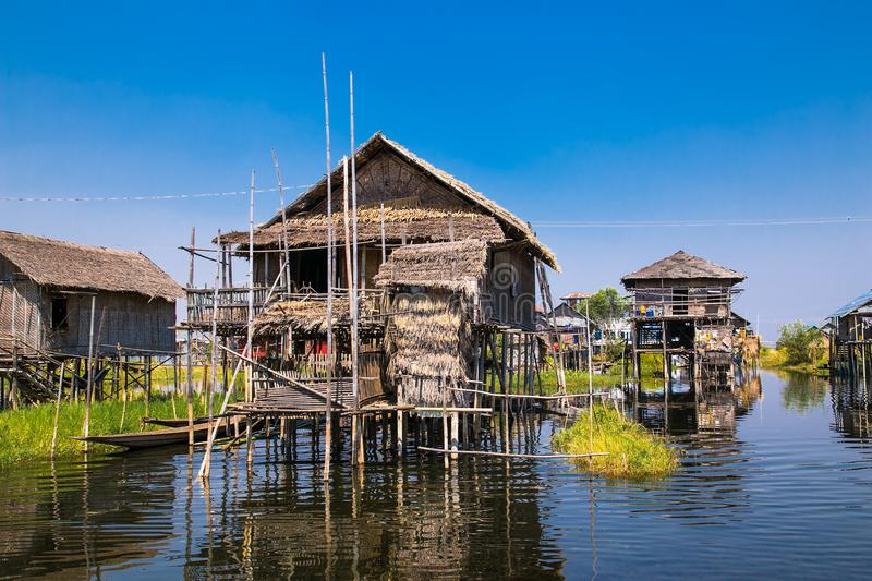 Ancient houses and their reflection in the water on the Inle Lake, Myanmar. stock photo