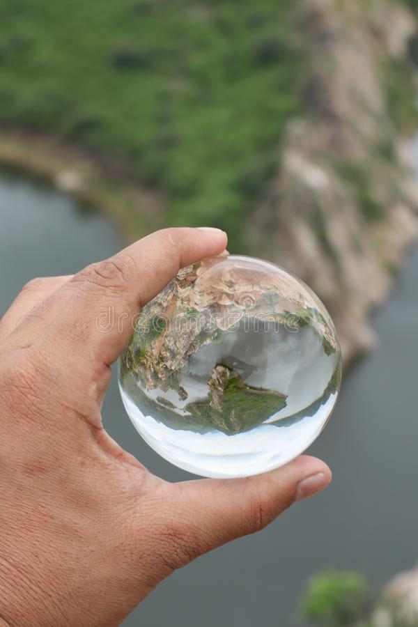 A man holding lensball in his hand with a reflection royalty free stock image