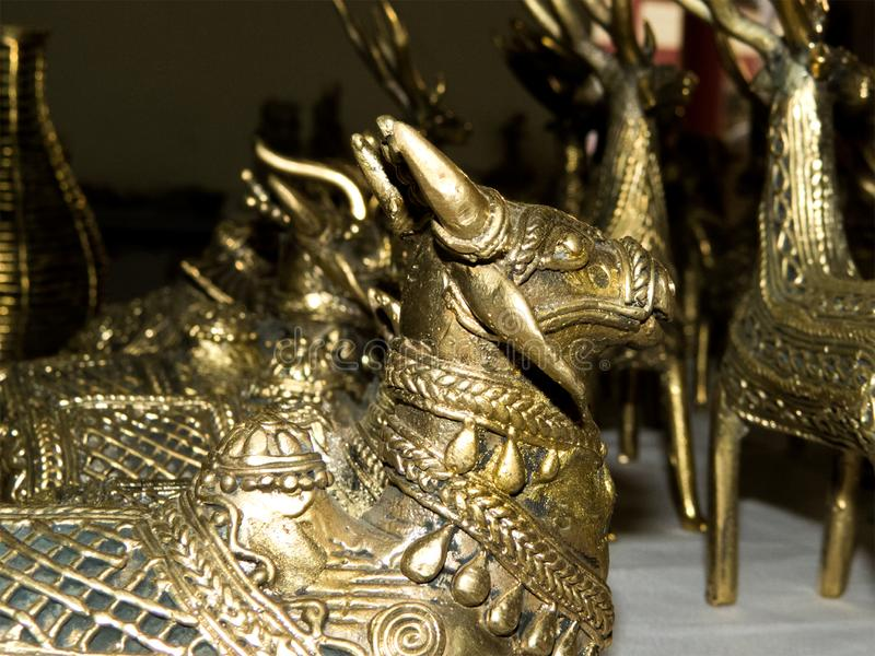 Brass metal sculptures Cow and Bull. Ancient Indian style sculpture of Cow and Bull made of brass metal. Created by tribal people of central India royalty free stock image