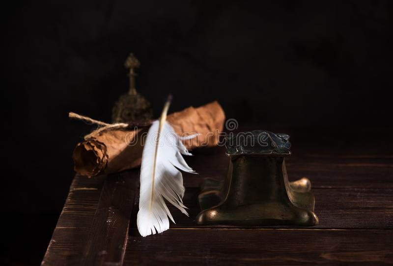 Ancient inkwell with a feather, old paper rolls for writing and bell. royalty free stock image
