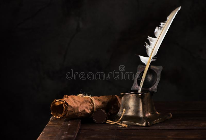 Ancient Inkwell, feather pen, old scroll paper with a seal royalty free stock photos