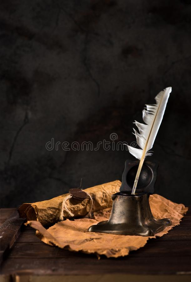 Ancient inkwell with feather pen and old writing paper stock image