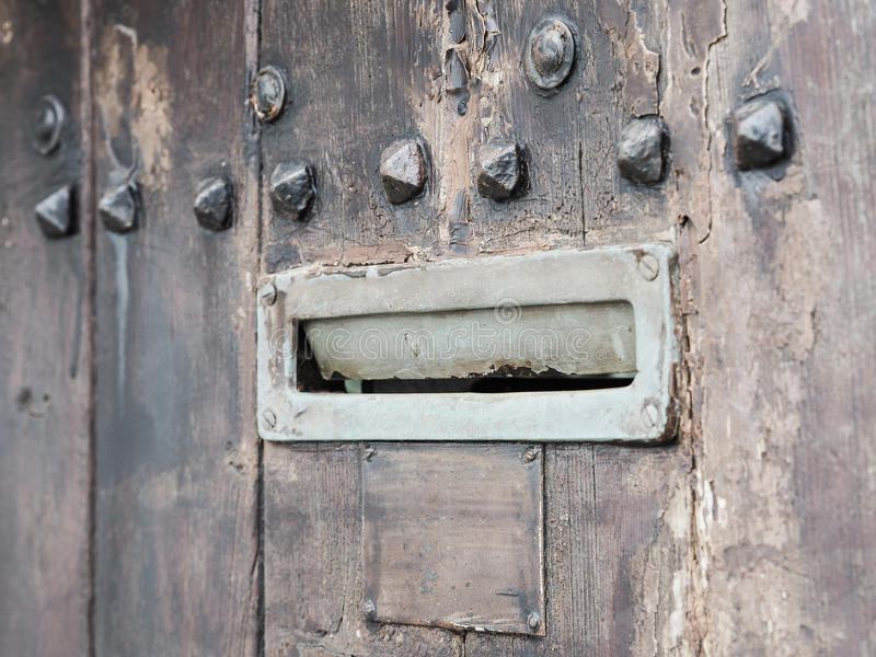 Ancient iron letterbox on brown wooden background. Ancient rusty iron letterbox opened on brown wooden door with metal ornaments, intentionally blurred stock photo