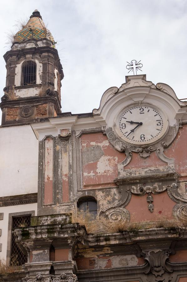 Ancient italian church with small cross and old clock. Time and religion concept. Vintage exterior building. Abandoned church. royalty free stock photography