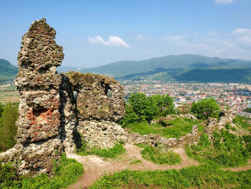 Ancient Khust fortress ruins on background of city and Carpathians stock images