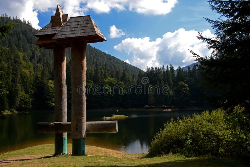 Ancient Lake Synevyr in the Ukrainian Carpathians surrounded by lush fairytale forest stock photography