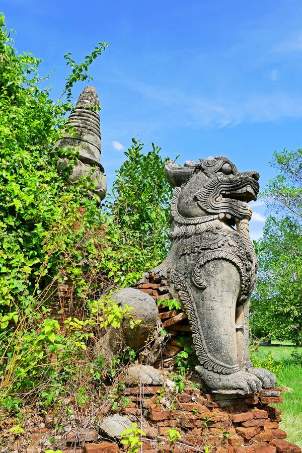 Lion Statue at Ancient Buddhist Pagoda Ruin in Inwa, Myanmar. Ancient Lion Statue of Abandon Ancient Buddhist Pagoda Ruin in the Paddy Fields in Inwa or Ava royalty free stock photo