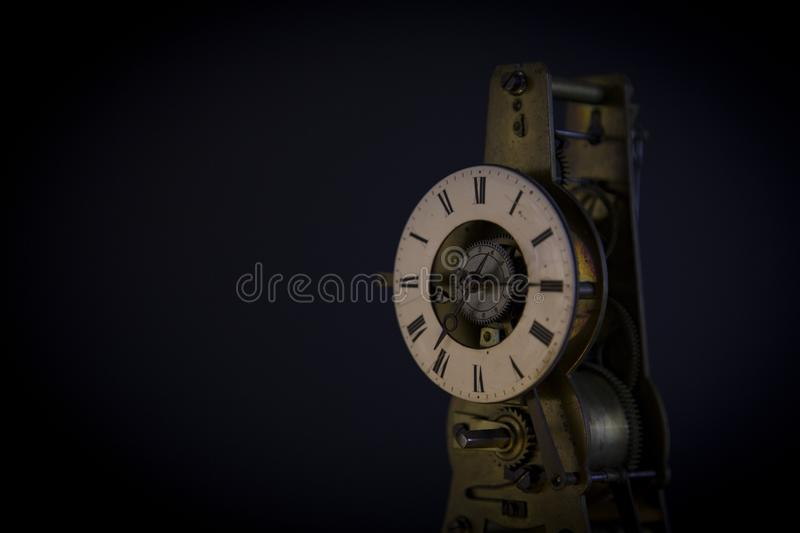 Ancient lusty watch mechanism. On a black background with hours royalty free stock photography