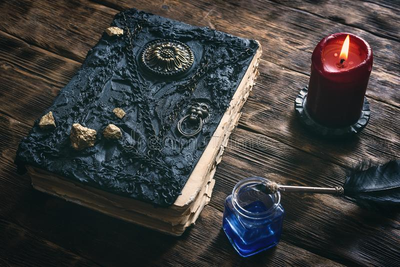 Magic book. Ancient magic book, ink well and a quill pen on a wooden table background. Spell book stock images