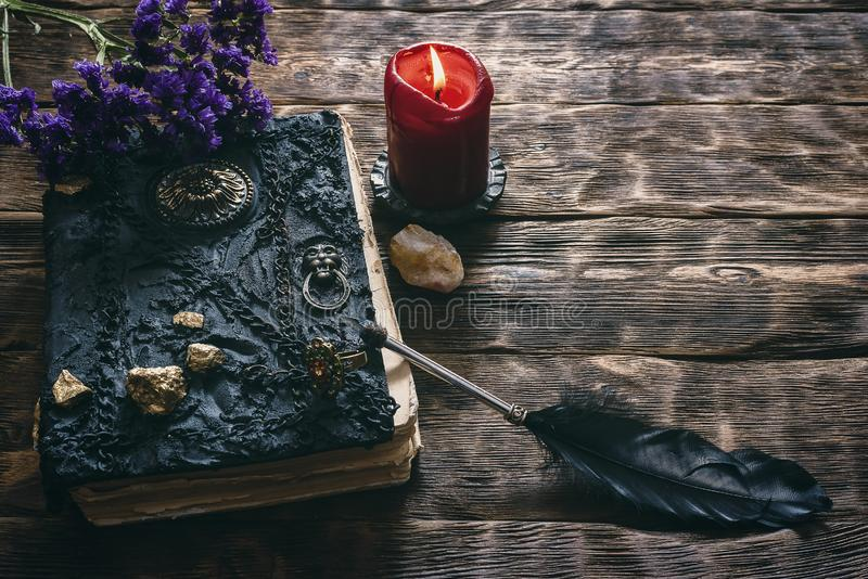 Book of magic. Ancient magic book, Limonium flower stem, inkwell and a quill pen on a wooden table background. Spell book royalty free stock photos