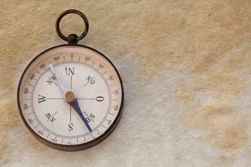 Ancient magnetic exploration compass, navigator. Manuscript aged paper background. copy space. closeup stock image
