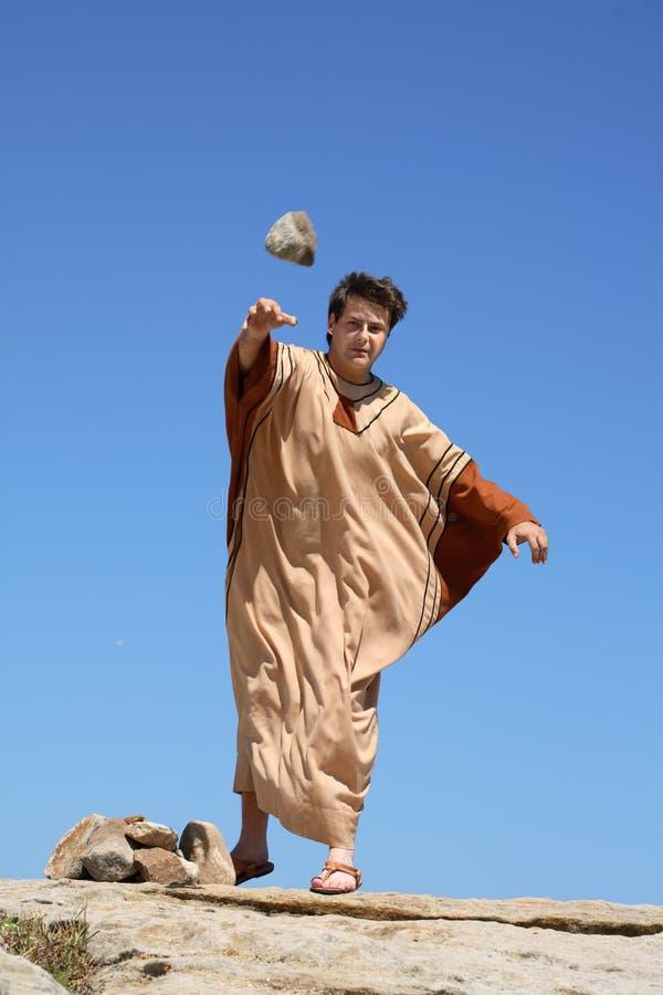 Ancient man throwing stone stock image
