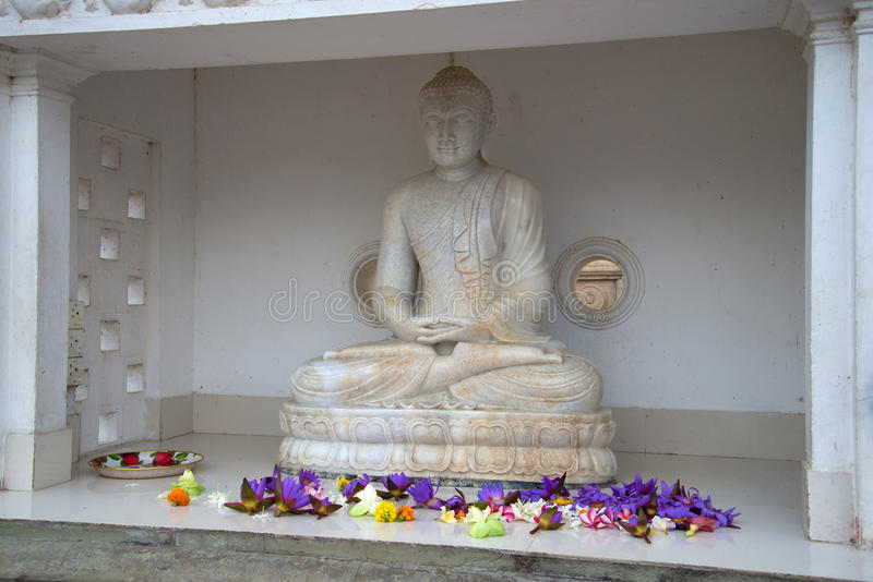 Ancient marble sculpture of a seated Buddha at the foot of the Dagoba Ruvanvelisaya. ANURADHAPURA, SRI LANKA - MARCH 12, 2015: Ancient marble sculpture of a royalty free stock image