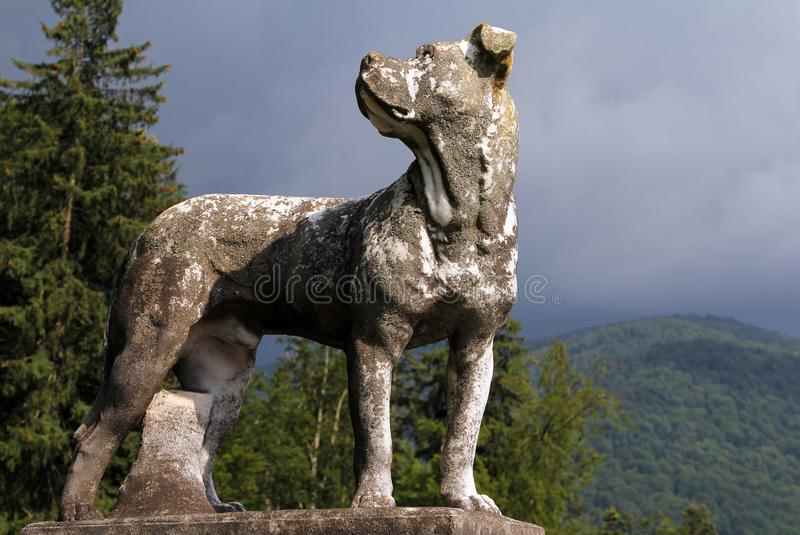 Ancient marble statue of a hunting dog on a background of Carpathian mountains, Peles Castle, Sinaia, Romania royalty free stock photos