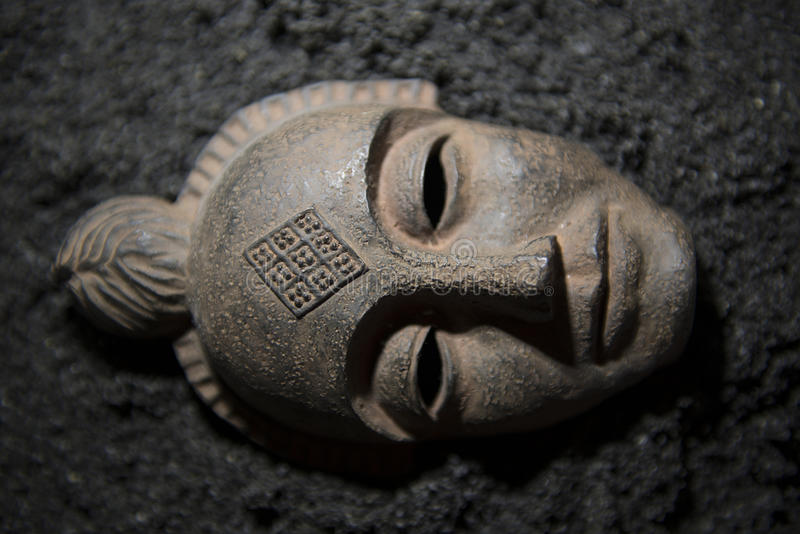 Ancient Mask. This is a replica mask decoration lying in volcanic sands royalty free stock images
