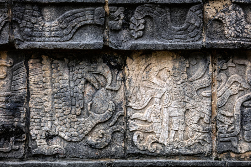 Ancient Mayan mural depicting an eagle grasping a human heart. And a warrior holding a human head on the Platform of the Skulls, a.k.a. Tzompantli in Chichen royalty free stock photography