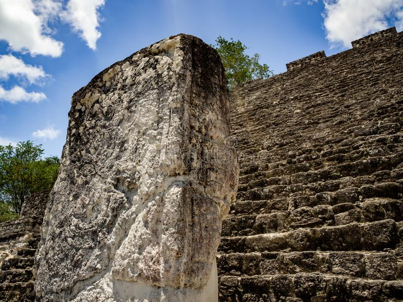 Ancient Mayan sculpture with hieroglyphic writing in Calakmul, M. Exico with clouds royalty free stock images