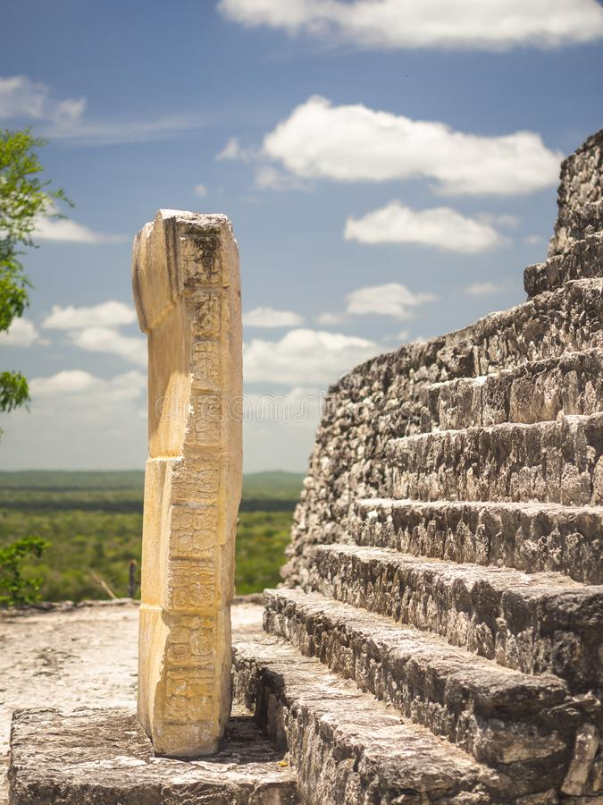 Ancient Mayan sculpture with hieroglyphic writing in Calakmul, M. Exico with clouds royalty free stock photos