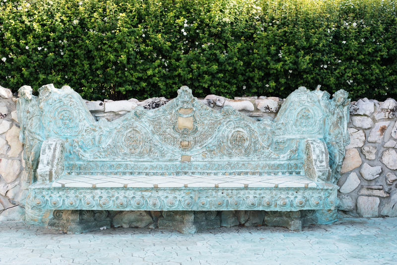 Ancient medieval baroque stone bench. Stone walkway. Alley in beautiful garden with flowers and trees around. Summer in the garden royalty free stock photos