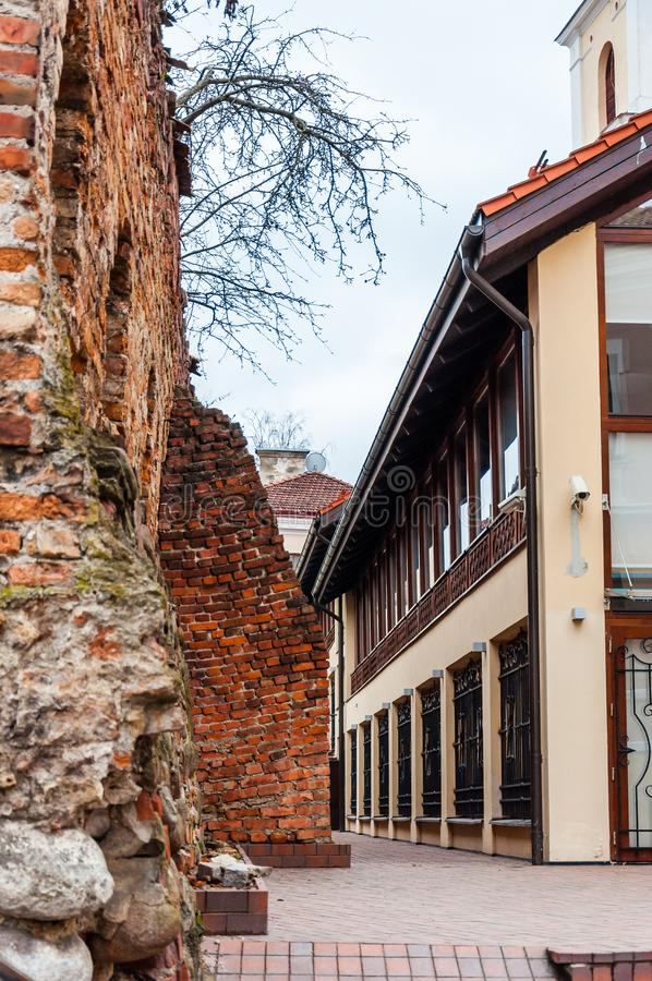 Ancient medieval ruined Old Town fortress wall near the European architecture business offices building on Subaciaus street in. Vilnius, Lithuania - April 28 stock images