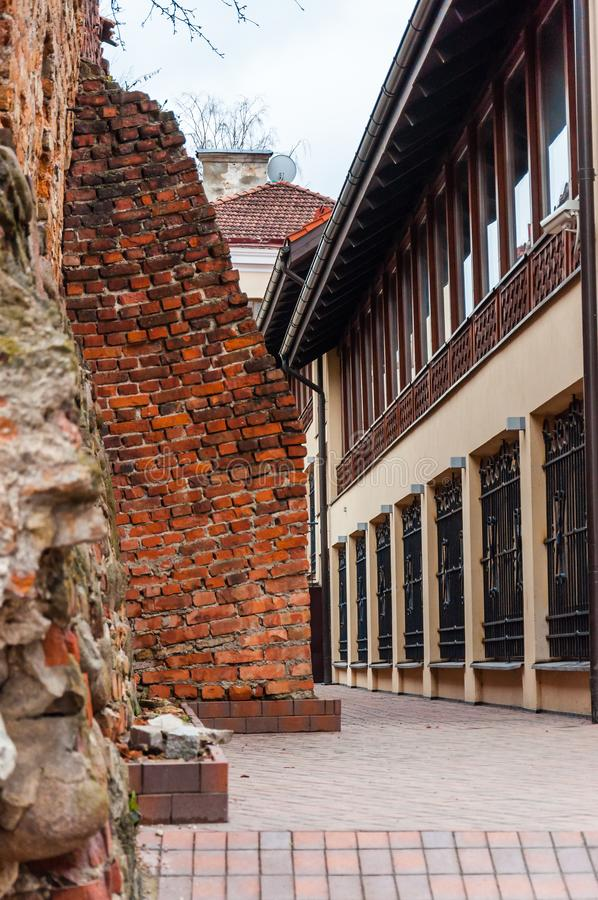 Ancient medieval ruined Old Town fortress wall near the European architecture business offices building on Subaciaus street in. Vilnius, Lithuania - April 28 royalty free stock photo