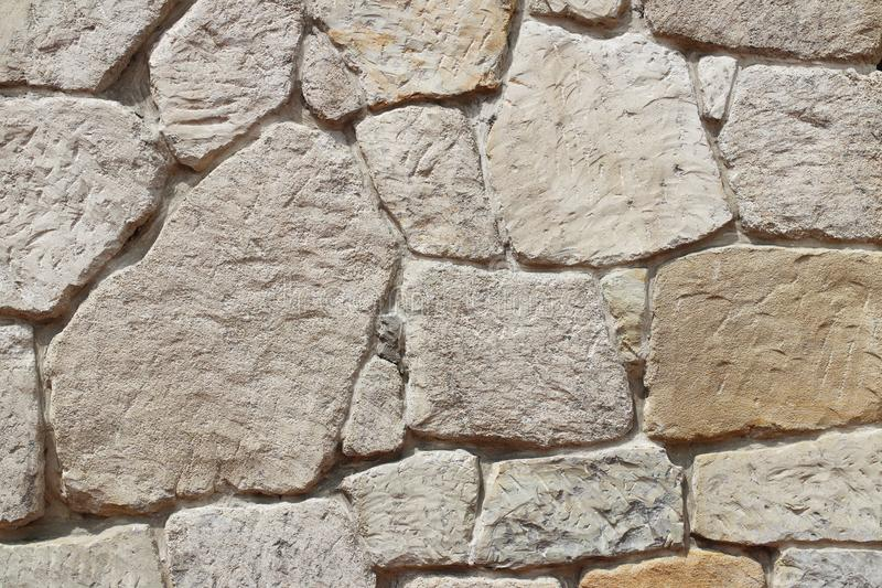 Ancient medieval stone masonry. Texture of a fragment of a wall of an old structure. A background for design and creative work. De stock photography