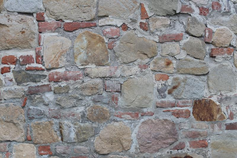 Ancient medieval stone masonry. Texture of a fragment of a wall of an old structure. A background for design and creative work. De royalty free stock images