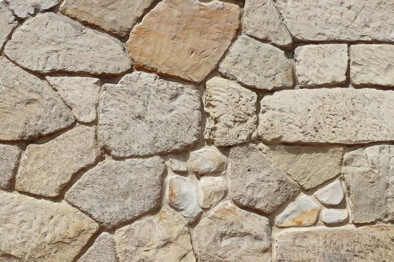Ancient medieval stone masonry. Texture of a fragment of a wall of an old structure. A background for design and creative work. De stock photo