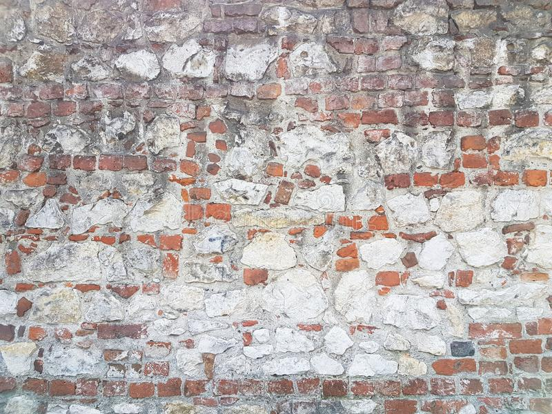 Ancient medieval stone masonry. Texture of a fragment of a wall of an old structure. A background for design and creative work. De royalty free stock photography