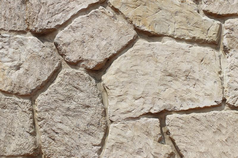 Ancient medieval stone masonry. Texture of a fragment of a wall of an old structure. A background for design and creative work. De royalty free stock image