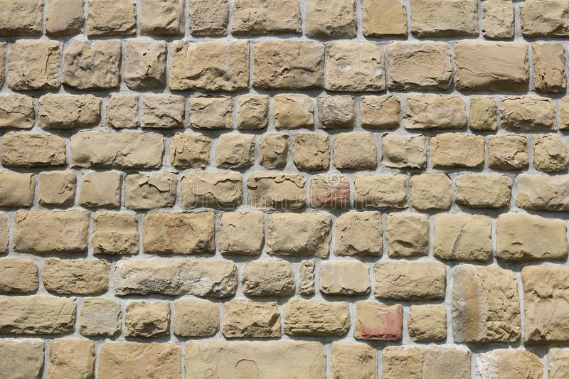 Ancient medieval stone masonry. Texture of a fragment of a wall of an old structure. A background for design and creative work. De royalty free stock photos