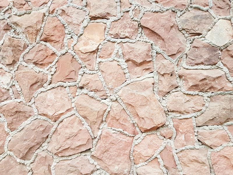 Ancient medieval stone masonry. Texture of a fragment of a wall of an old structure. A background for design and creative work. De royalty free stock photo