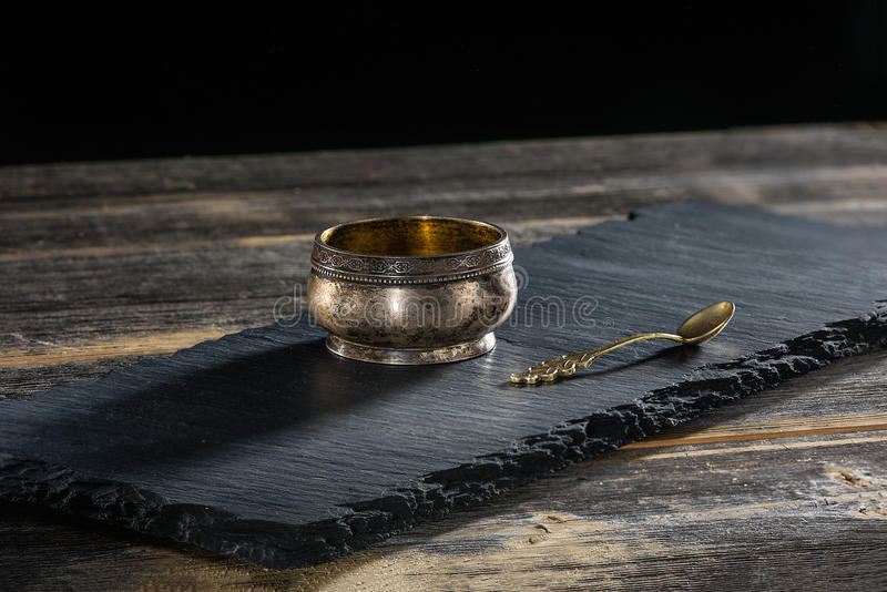 Ancient melkhiorovy saltcellar with spoon on a black slate plate in style rustic. Ancient melkhiorovy saltcellar with a beautiful spoon on a black slate plate in stock photos