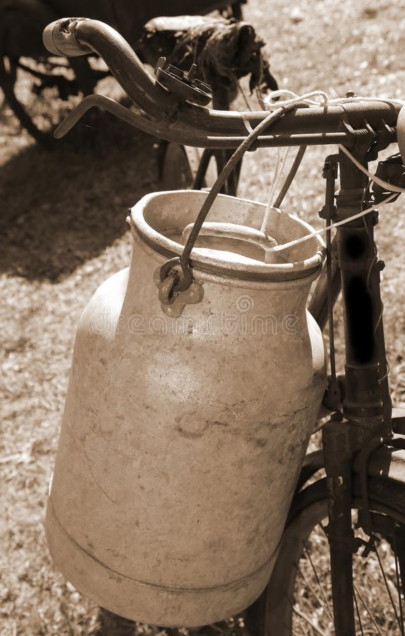 Ancient milking bicycle with milk can and ancient sepia tone stock photos