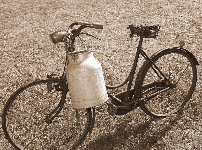 Ancient milking bicycle with milk can and ancient sepia effect royalty free stock photo