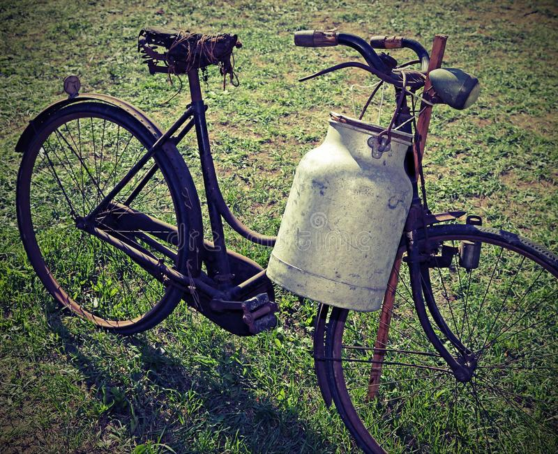 Ancient milking bike with milk bin and vintage effect stock photos