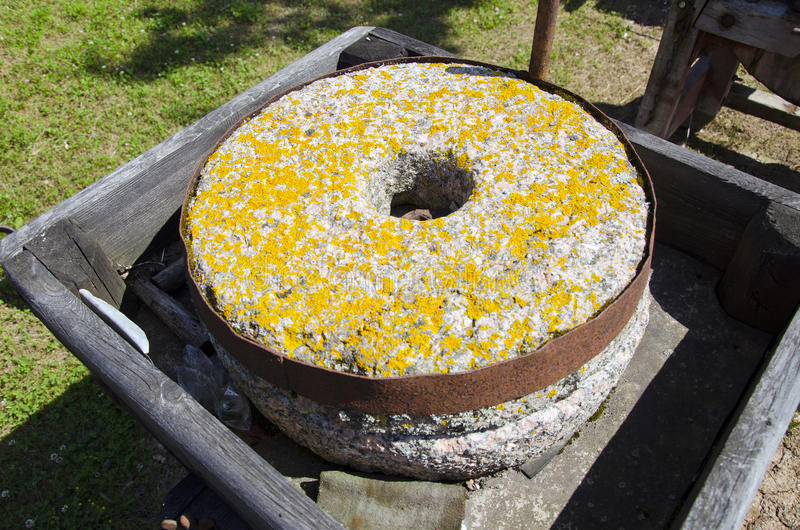 Ancient millstone with yellow lichens stock photo
