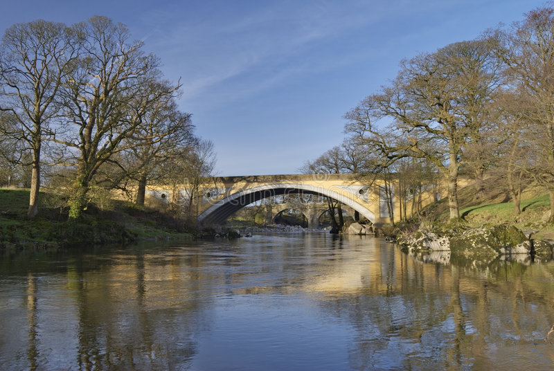 Ancient and modern bridges. The medieval Devils bridge seen through the modern road gridge on the river Lune near Kirkby Lonsdale, Cumbria, UK stock images