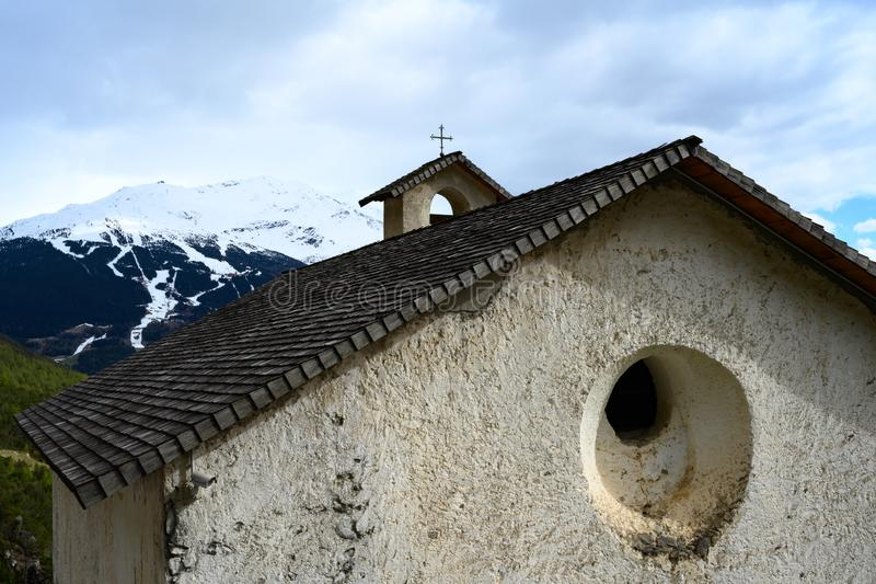 Ancient monastary in the Alps. Shingled roof and cross on an old monastary in the Italian Alps with snow covered ski slope on distant mountain royalty free stock images