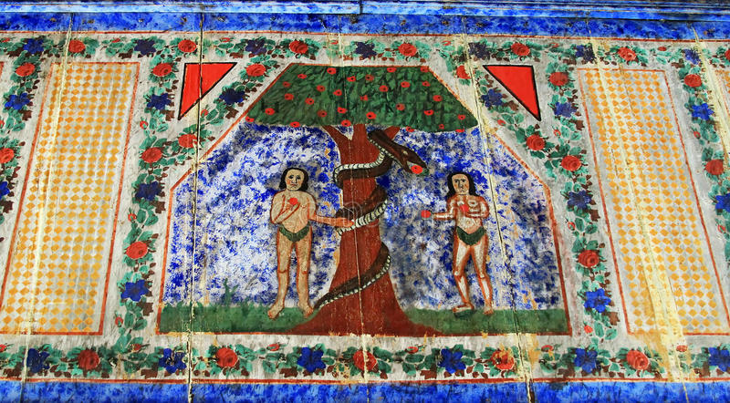 Mural Fresco. Ancient mural fresco on wood with Adam and Eve in Maramures, Romania stock photo