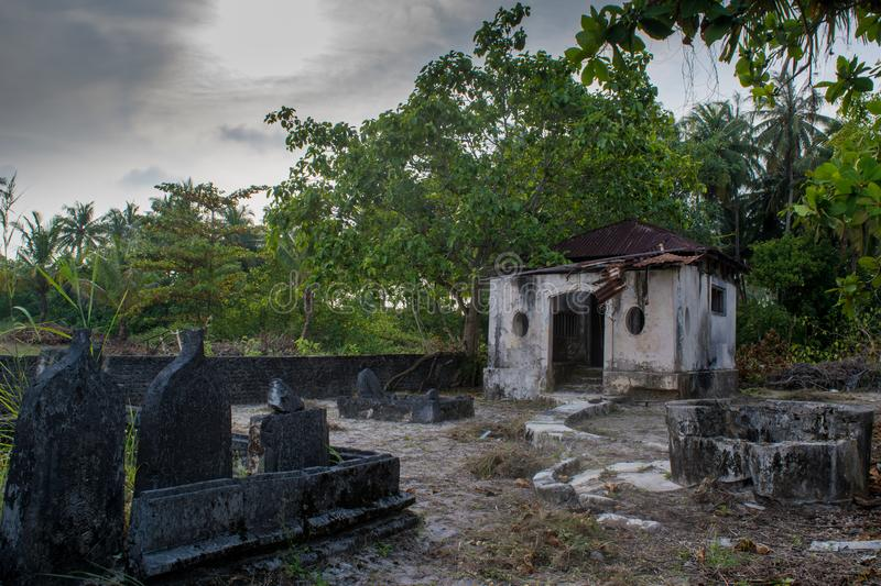 Ancient old creepy cemetery with crypt and graves at the tropical local island Fenfushi. Ancient old creepy abandoned cemetery with crypt and graves at the stock photo