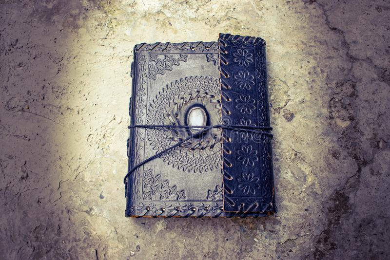 Ancient old leather bound book lying on the ground royalty free stock images